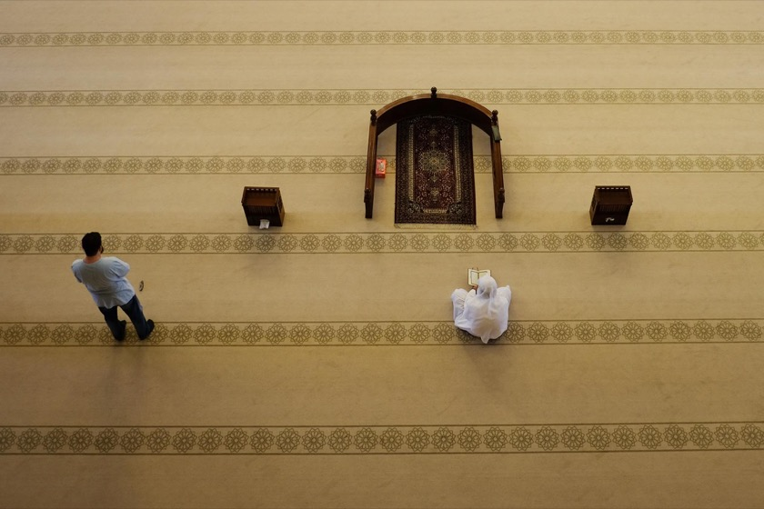 Two men praying inside the Al Fateh Grand Mosque.